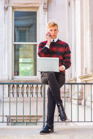 Young American man studying, working in New York, wearing patterned knit sweater, black pants, leather shoes, sitting on railing in office building, working on laptop computer, talking on cell phone. Фото со стока