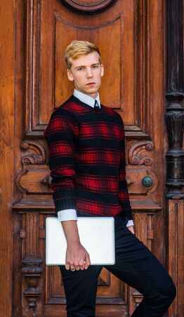 Young blonde American male college student wearing patterned red, black knit sweater, holding laptop computer, standing by brown vintage wooden office door, looking at you.