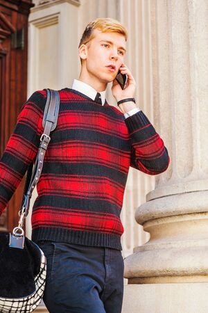 Young blonde American businessman wearing patterned red, black knit sweater, carrying bag on shoulder, walking out from office building, talking on cell phone