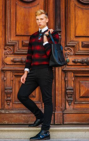 Young blonde American college student wearing patterned red, black knit sweater, black pants, glasses hanging on collar, holding leather bag on shoulder, standing by brown vintage wooden office door.