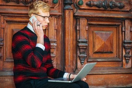 Young  blonde American college student wearing patterned red, black knit sweater, glasses, sitting by brown vintage wooden office door, working on laptop computer, talking on cell phone.