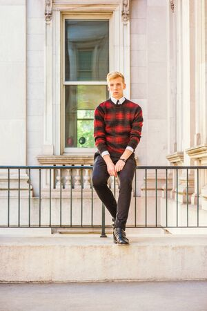 Young blonde American college student wearing patterned red, black knit sweater, black pants, leather shoes, sitting by railing in vintage office building in New York, relaxing, taking work break.