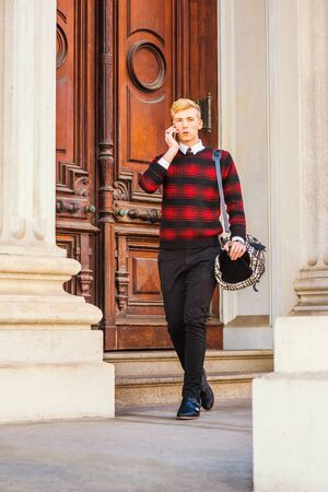 Young blonde American businessman wearing patterned red, black knit sweater, black pants, leather shoes, carrying bag on shoulder, walking by vintage office door way, talking on cell phone Фото со стока
