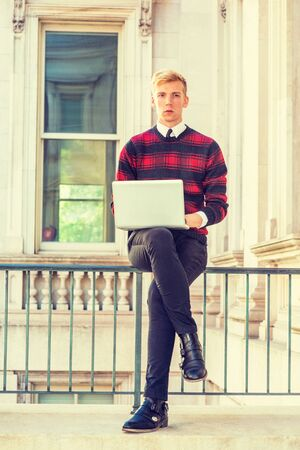 Young blonde American college student studying in New York, wearing patterned red, black knit sweater, black pants, leather shoes, sitting on railing in office building, working on laptop computer.