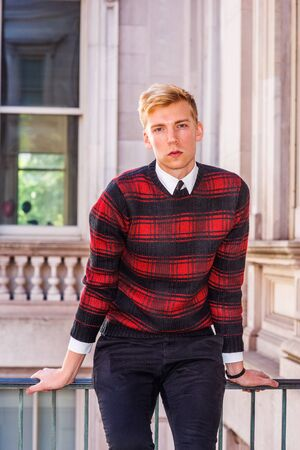 Young blonde American college student wearing patterned red, black knit sweater, sitting by railing in vintage office building in New York, relaxing, taking work break. Фото со стока