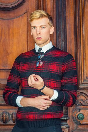 Young blonde American male college student wearing patterned red, black knit sweater, glasses hanging on collar, standing by brown vintage wooden office door, confidently looking at you.