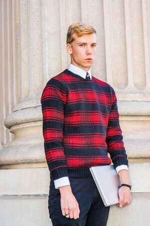 Young blonde American male college student wearing patterned red, black knit sweater, holding laptop computer, standing by column outside, looking  at you.