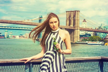 Young Woman missing you, waiting for you, holding white rose, wearing black, white striped dress, long hair float in air, standing by river in New York. Manhattan, Brooklyn bridges on background.