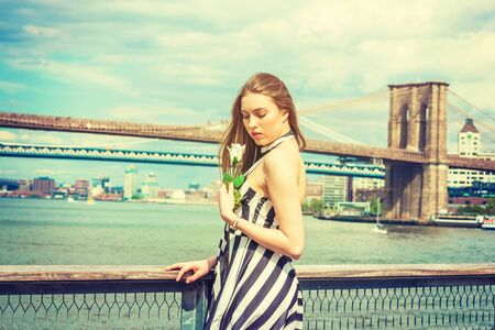 Young Beautiful Woman missing you, holding white rose, wearing black, white striped dress, standing by river in New York, looking down, sad, thinking. Manhattan, Brooklyn bridges on background.