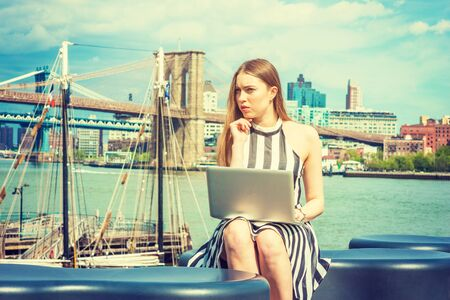 Young European Woman traveling, working in New York, wearing black, white striped dress, sitting by river, working on laptop computer, hand touching chin, thinking. Brooklyn bridge on background.