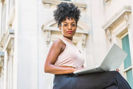 Way to Success. Young African American woman with afro hairstyle wearing sleeveless light color top, sitting by vintage office building in New York, working on laptop computer, looking, thinking.
