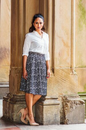 Portrait of Young Beautiful East Indian American Woman in New York, wearing white shirt, black and white patterned skirt, high heals, standing by vintage column, turning around, looking at you.