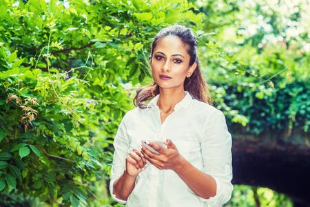 Young Beautiful East Indian American Woman texting on cell phone outdoor at Central Park, New York, wearing white shirt, standing in front of street bridge with green leaves, looking up, thinking.
