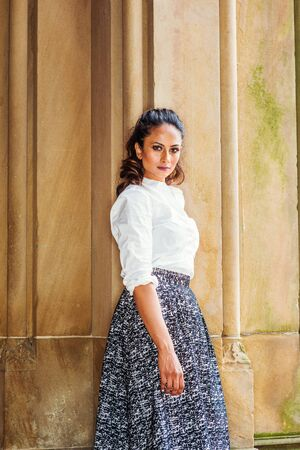 Portrait of Young Beautiful East Indian American Woman in New York, wearing white shirt, black and white patterned skirt, standing by vintage column, turning around, looking at you. Archivio Fotografico