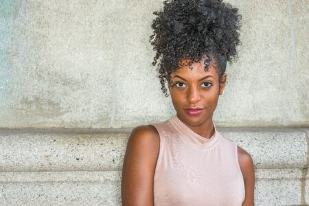 Portrait of Young African American Woman in New York. Young black female college student with afro hairstyle wearing sleeveless light color top, standing against vintage wall, looking at you.