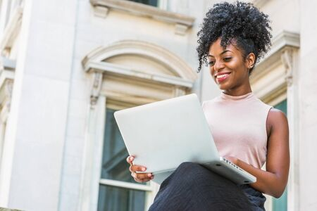 Way to Success. Young African American woman with afro hairstyle wearing sleeveless light color top, sitting by vintage office building in New York, looking down, working on laptop computer, smiling. Stock Photo