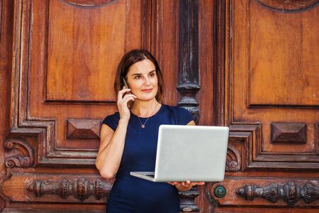 Young Happy Native American Businesswoman working in New York, wearing short sleeve dress, necklace, standing by vintage office door, working on laptop computer, talking on cell phone, smiling.
