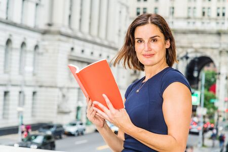 Reading outside. Young 40 years old Native American woman wearing short sleeve dress, standing on street by old style office building in New York City, reading red book, looking away, thinking.