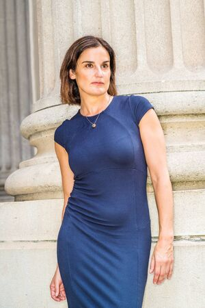 Portrait of Young 40 years old Native American Businesswoman in New York City. Young beautiful woman wearing blue short sleeveless dress, necklace, standing by column outside office building, looking.