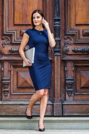 Young Native American Businesswoman working in New York, wearing blue short sleeve dress, necklace, carrying laptop computer, walking down stairs by brown vintage office door, talking on cell phone.