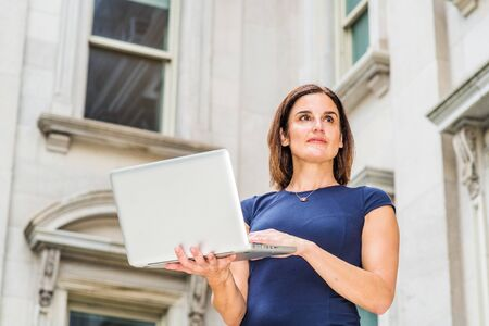 Young 40 years old Native American Businesswoman working in New York City, wearing short sleeve dress, holding laptop computer, standing outside office building with windows, looking up, thinking.