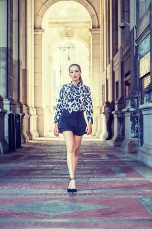 Young American Woman Street Fashion in New York City. South American College Student with ponytail hairstyle, wearing long sleeve patterned shirt, black short skirt, walking on narrow vintage street.  Stock fotó