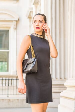Young South American Businesswoman working in New York City, wearing black sleeveless dress, shoulder carrying leather bag, standing inside old style of vintage office building, talking on cell phone. Stock fotó