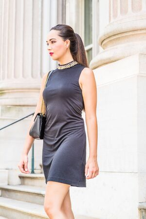 Young American Businesswoman Fashion. Young South American Woman working in New York City, wearing black sleeveless dress, shoulder carrying leather bag, walking down stairs from office building. Stock fotó