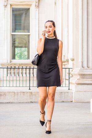 Go to Work. Young South American Businesswoman working in New York City, wearing black sleeveless dress, shoulder carrying leather bag, walking inside vintage office building, talking on cell phone.