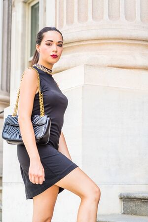 Go to Work. Young South American Businesswoman working in New York City, wearing black sleeveless dress, shoulder carrying leather bag, walking up stairs, going to office building, looking away.