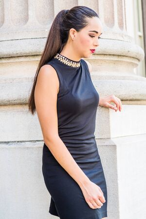 Young unhappy, serious Hispanic Woman with ponytail hairstyle, wearing black sleeveless dress, standing against column outside office building on campus in New York City, looking down, sad, thinking.
