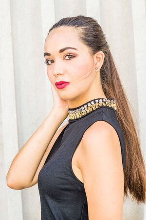 Portrait of South American Female College Student in New York City. Young Beautiful Hispanic Woman wearing black sleeveless dress, standing by column outside office building. Close Up Head Shot