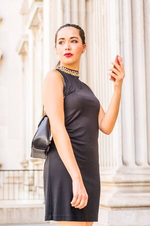 Young South American Businesswoman working in New York City, wearing black sleeveless dress, shoulder carrying leather bag, standing inside old style of office building, holding cell phone, looking.