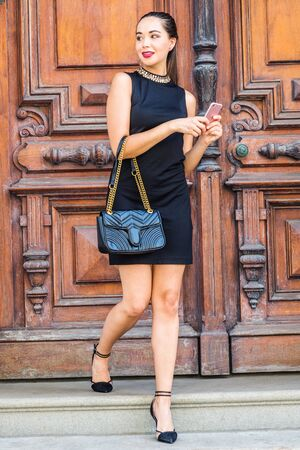 Young South American Businesswoman working in New York City, wearing black sleeveless dress, arm carrying leather bag, walking dow stairs by brown vintage wooden office door, texting on cell phone.  Stock fotó
