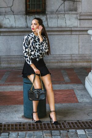 South American Woman traveling, relaxing in New York City, wearing long sleeve patterned shirt, black short skirt, high heels, sitting on pillar on street, holding leather bag, talking on cell phone. Stock fotó