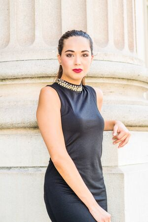 Portrait of South American Female College Student in New York City. Young Beautiful Hispanic Woman wearing black sleeveless dress, standing against column outside office building on campus, looking.