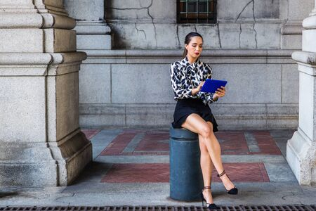 South American Woman relaxing outside in New York City, wearing long sleeve patterned shirt, black short skirt, high heels, sitting on pillar on street, holding blue tablet computer, looking, reading.