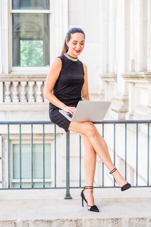 South American Female College Student studying in New York City. Young Hispanic Woman wearing black sleeveless dress, high heels, sitting inside office building on campus, working on laptop computer.