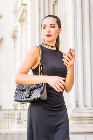 Young South American Businesswoman working in New York City, wearing black sleeveless dress, shoulder carrying leather bag, standing inside old style of office building, holding cell phone, looking. Stock fotó