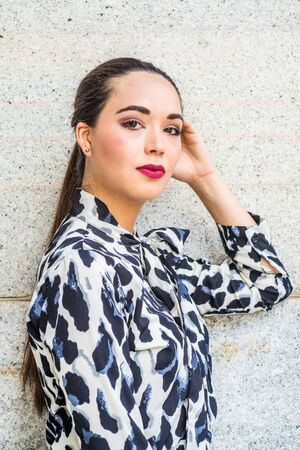 Portrait of South American Female College Student in New York City. Young Beautiful Hispanic Woman with ponytail hairstyle, wearing patterned shirt, standing against wall outside, looking, thinking. Stock fotó