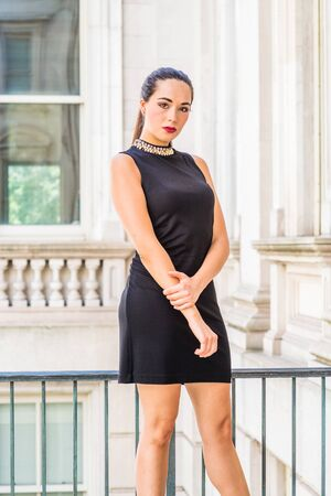 Portrait of South American Female College Student in New York City. Young Beautiful Hispanic Woman wearing black sleeveless dress, standing inside vintage office building with window, looking forward.
