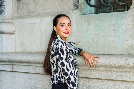 Portrait of South American Female College Student in New York City. Young Beautiful Hispanic Woman wearing long sleeve patterned shirt, standing against wall on campus, turning back, looking, smiling.