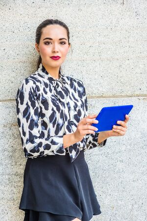 Modern Reading. South American Female College Student studying in New York City, wearing long sleeve patterned shirt, black short skirt, standing against wall, holding blue tablet computer, reading.