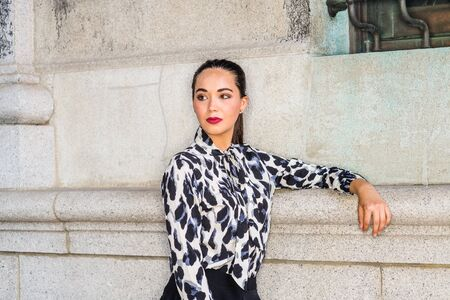 Portrait of Young South American Female College Student in New York City. Young Beautiful Hispanic Woman wearing long sleeve patterned shirt, standing against wall on campus, looking away, thinking.