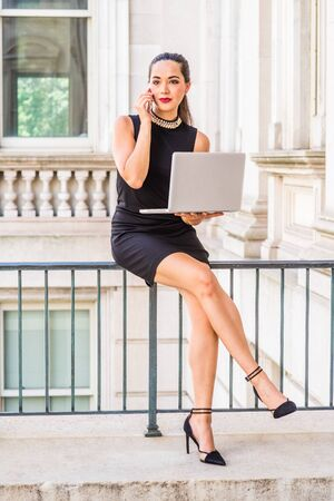 South American College Student studying, working in New York, wearing black sleeveless dress, high heels, sitting inside office building on campus, working on laptop computer, talking on cell phone. Stock fotó