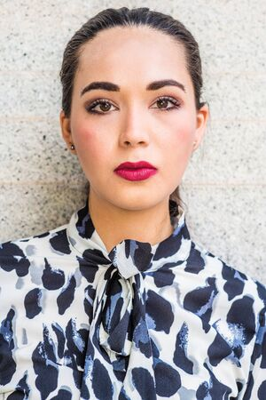 Portrait of South American Female College Student in New York City. Young Beautiful Hispanic Woman with ponytail hairstyle, wearing patterned shirt, standing against wall outside. Close Up Head Shot
