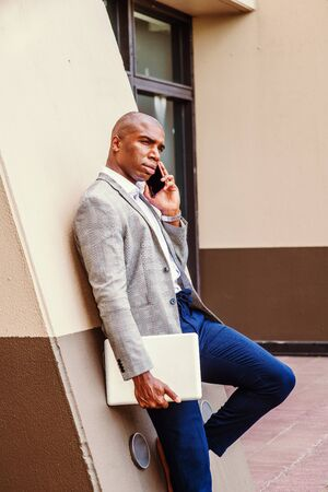 Young African American Business Man working in New York City, wearing gray blazer, blue pants, carrying laptop computer, standing against column outside office building, talking on cell phone,