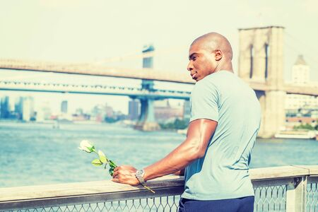 Welcome You. I miss you. Young African American Man wearing gray T shirt. holding white rose, standing by fence at harbor in New York City, waiting for you. Manhattan, Brooklyn bridges on background.