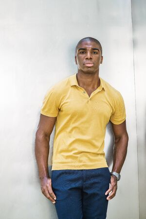 Portrait of Young African American Man in New York City. Wearing yellow short sleeve shirt, young black college student with afro short hair,  standing against silver metal wall on campus, thinking.
