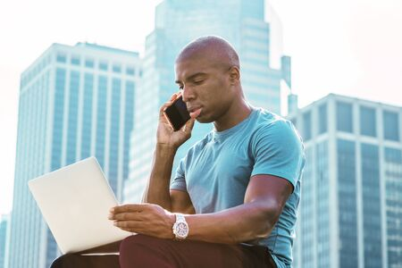 Young African American Businessman traveling, working in New York, wearing blue T shirt, sitting in front of business district, looking down, working on laptop computer, talking on cell phone. Stock fotó